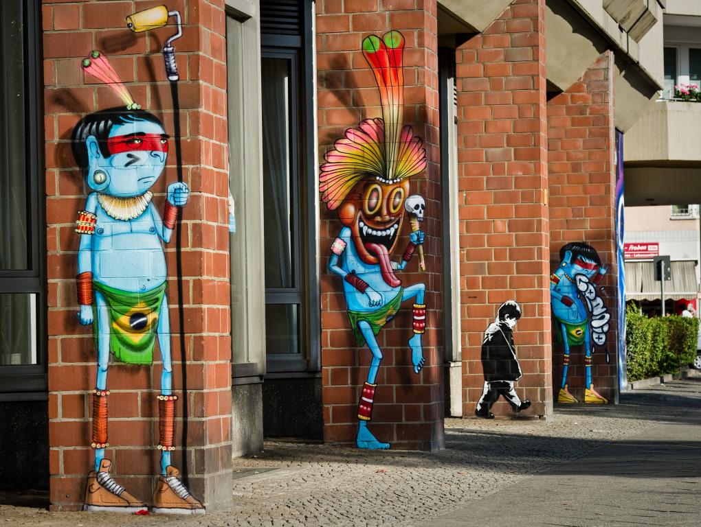 Figuren von Urban Nation Künstlern an Backsteinsäulen
