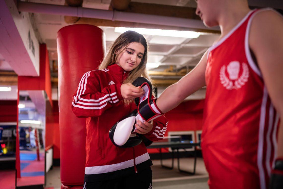 Mädchen zieht Jungen Boxhandschuh beim Projekt Wir aktiv Boxsport an