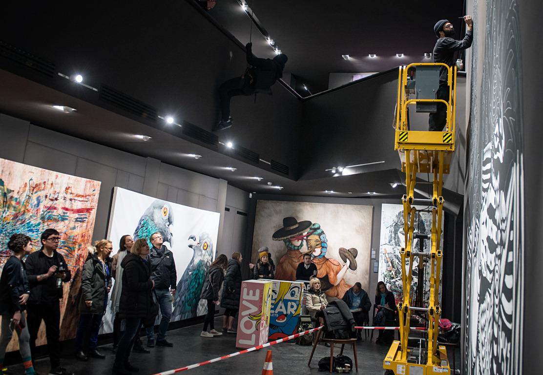 Künstler malt auf Hebebühne ein Bild in die Galerie bei Urban Nation Berlin