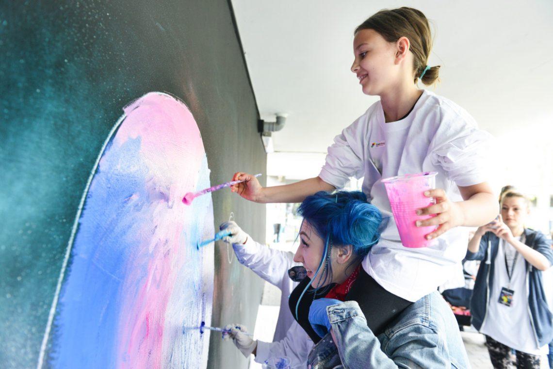 Kinder sind Huckepack und malen ein Bild bei Urban Nation Berlin