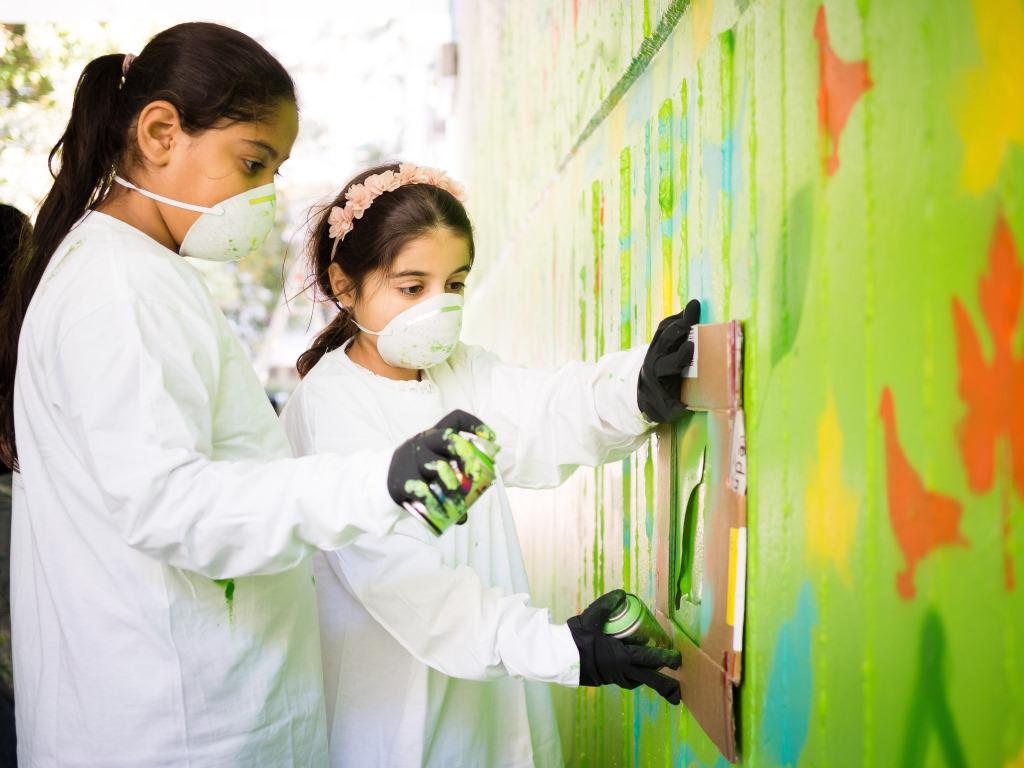 Kinder mit Gesichtsschutz sprühen ein Bild bei Urban Nation Berlin