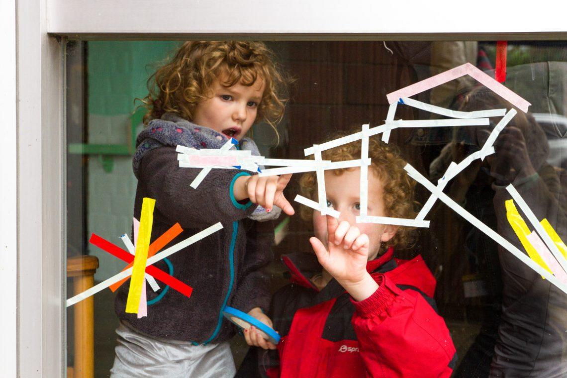 Kinder bekleben eine Fensterscheibe mit bunten Streifen