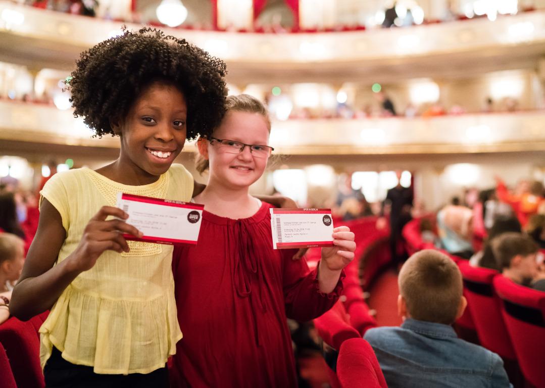 Kinder mit Theaterkarten beim Projekt Abenteuer Oper 77 Zwerge