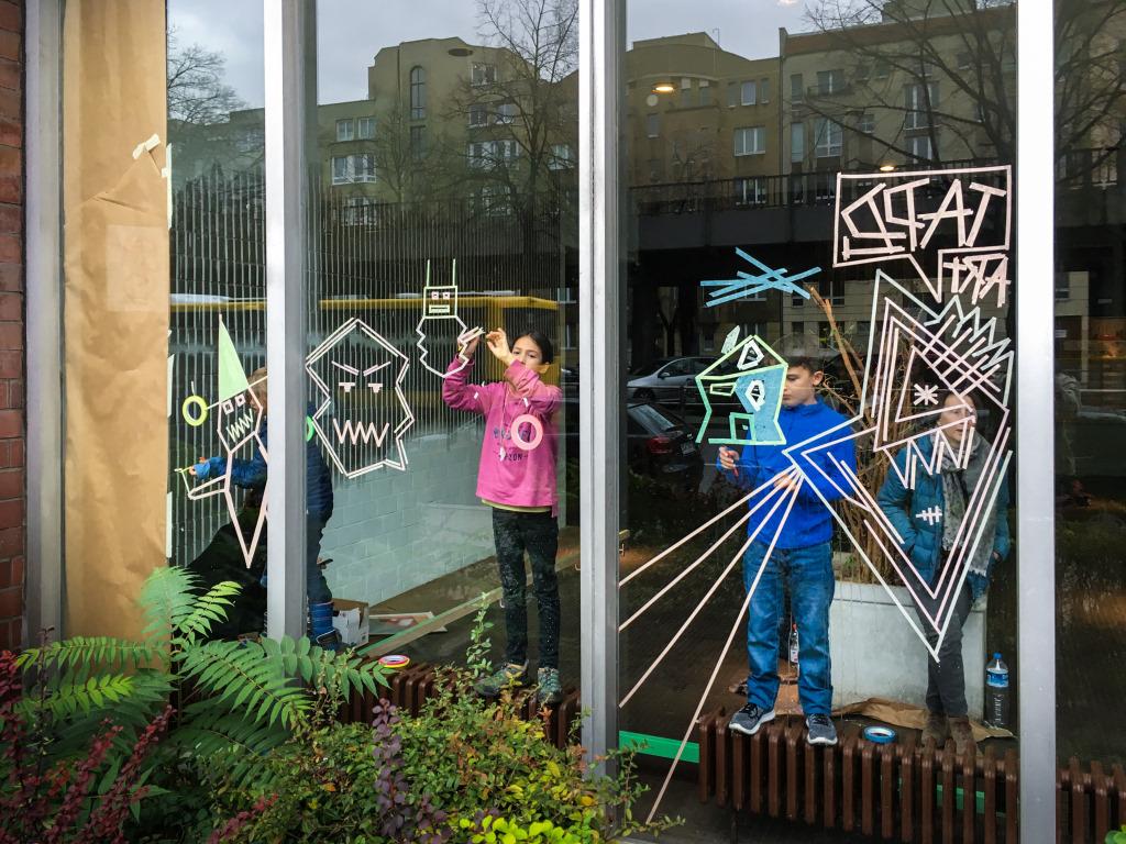 Kinder kleben Fensterbilder an Fensterscheiben beim Tape-Art-Workshop