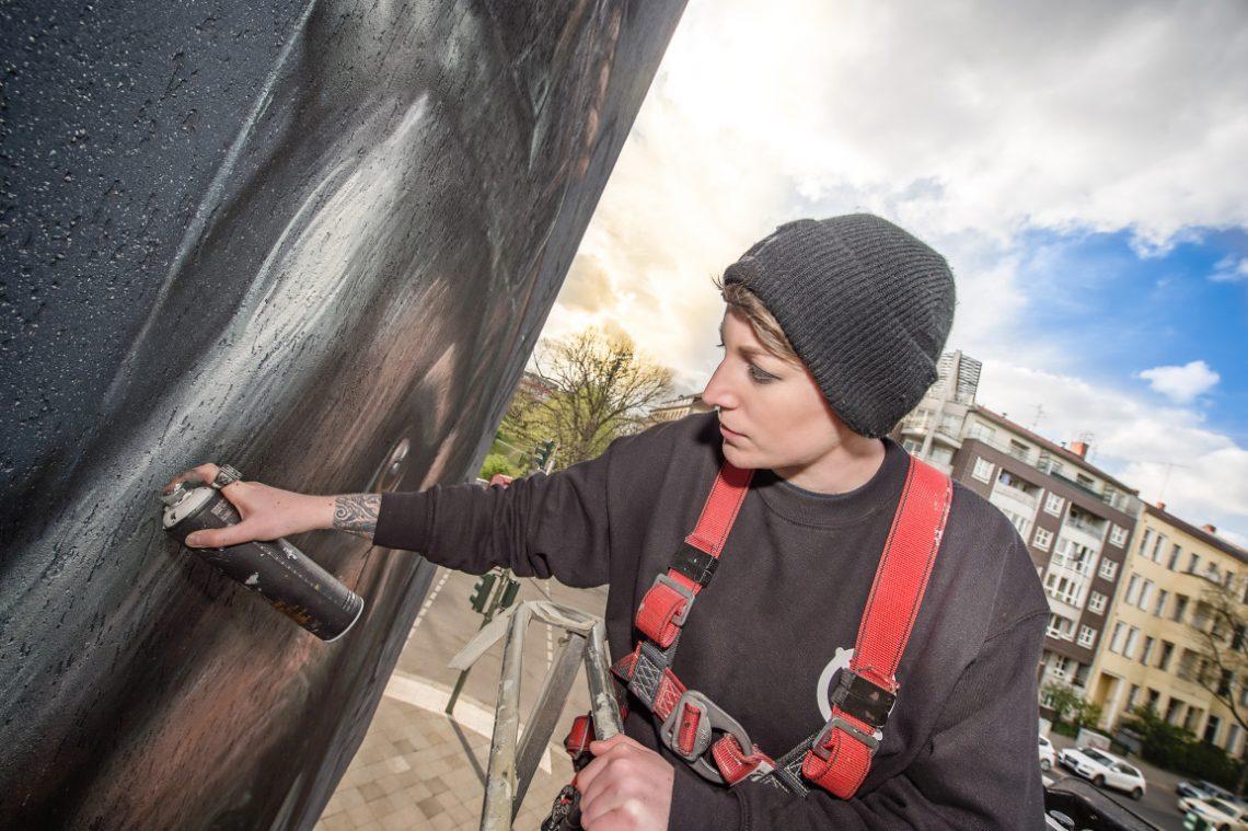 Künstlerin malt bei Urban Nation Bild mit Sprühdose an Hauswand