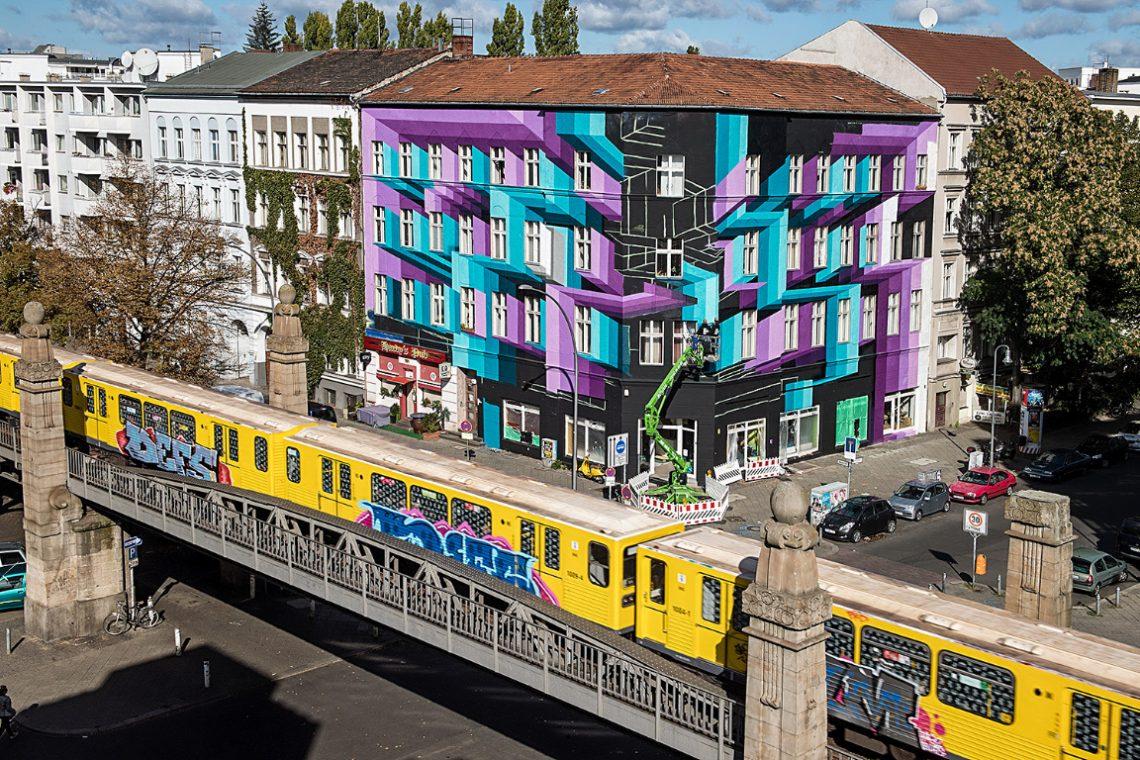 Künstler malt Kunstwerk an Hausfassade in Berlin