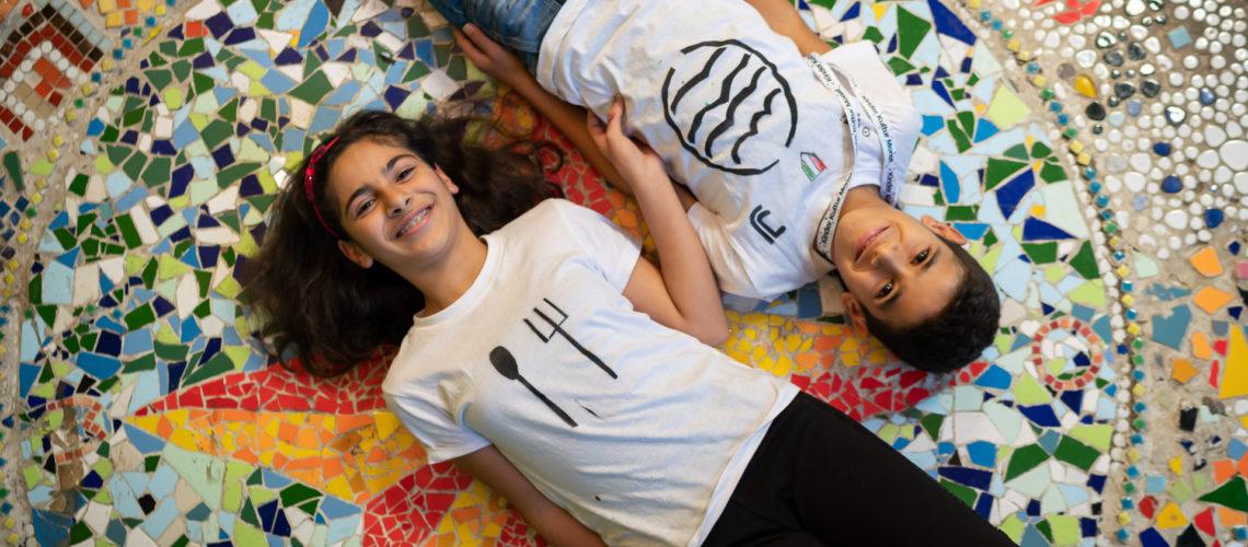 Junge und Mädchen liegen auf Mosaik beim KinderKulturMonat