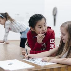 Vier Mädchen sitzen an einem Tisch und malen mit Stiften auf Papier.