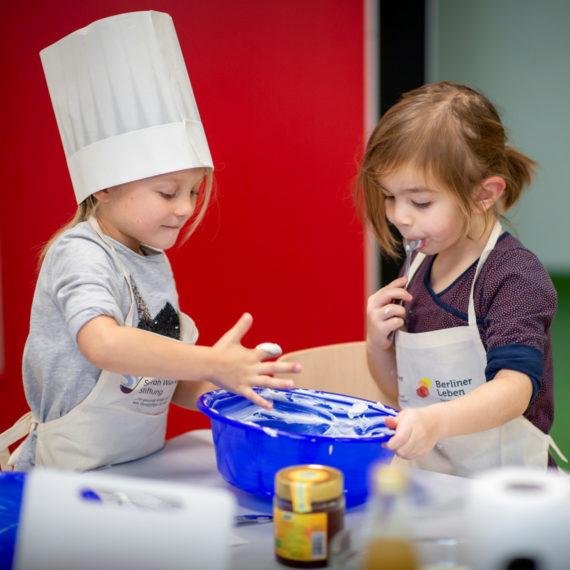 Backende Kinder mit Schürze der Stiftung Berliner Leben