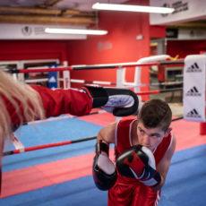 Jugendlicher geht im Boxring bei einem Schlag in Deckung