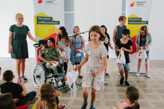 Stehende und laufende Kinder vor Stiftung Berliner Leben Aufsteller