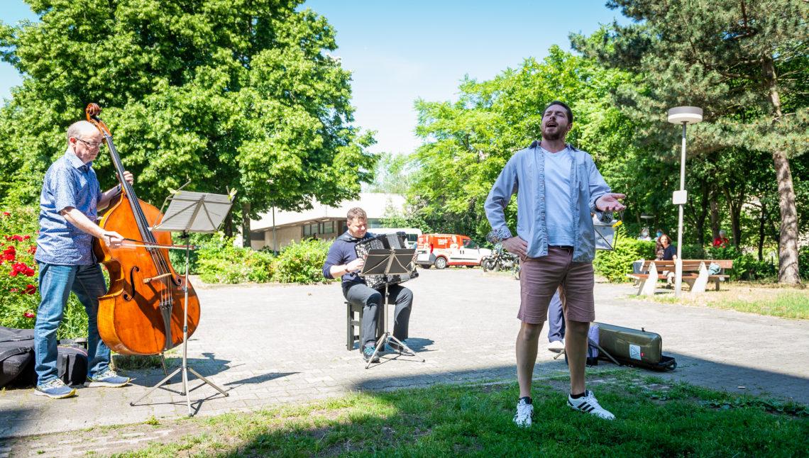 Ein Mann singt begleitet von einem Musikanten-Trio auf der Straße.