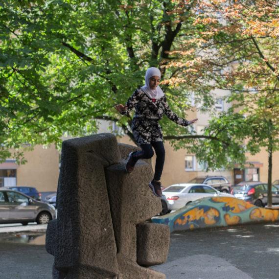 Mädchen springt von einer Skulptur
